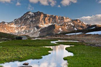 Méandres et petits marais devant l'imposante masse de pierre du Sasseneire qui culmine à  3254 mètres.