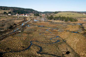 Vue aérienne d'un secteur renaturé où la Lemme de 1,5-2m de large serpente à nouveau dans le marais. Au fond à gauche, l'ancien tracé rectiligne et large de 6-7m avant son effacement.