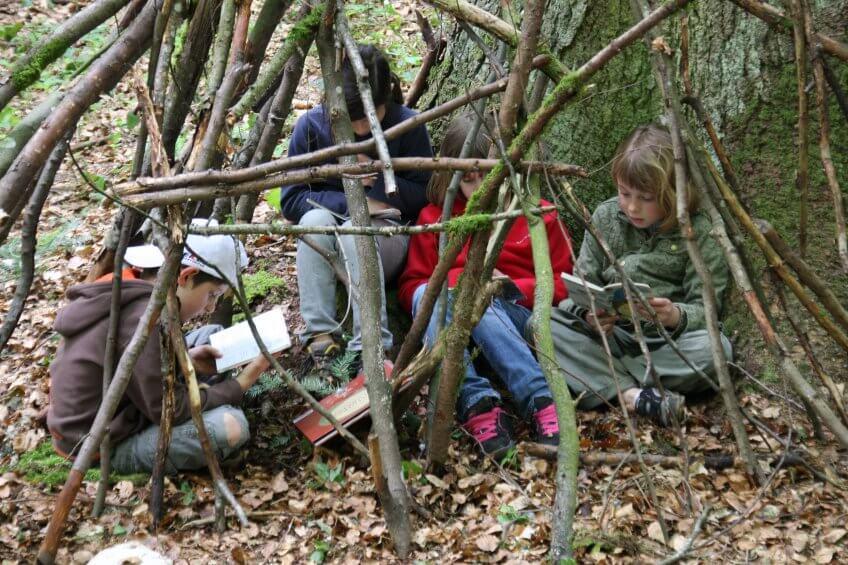 Des enfants lisent dans la nature.