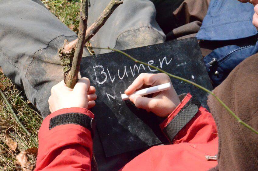 Un enfant écrit sur un tableau.