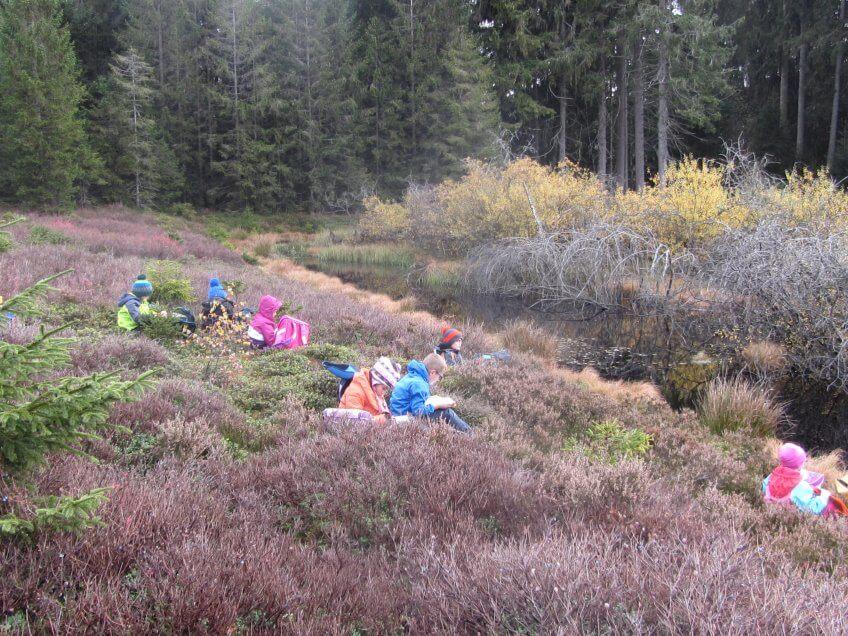 Des enfants écrivent un poème dans la nature.