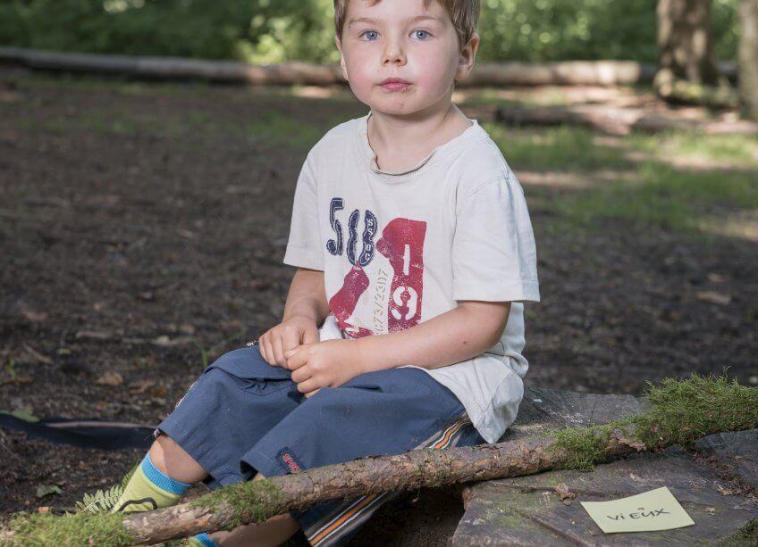Un enfant qui a trouvé deux cartes avec des adjectifs contraires.