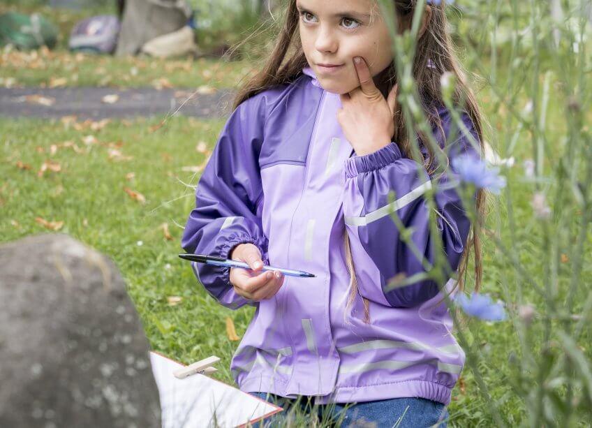 Une enfant écrit une histoire mouvementée dans la nature.