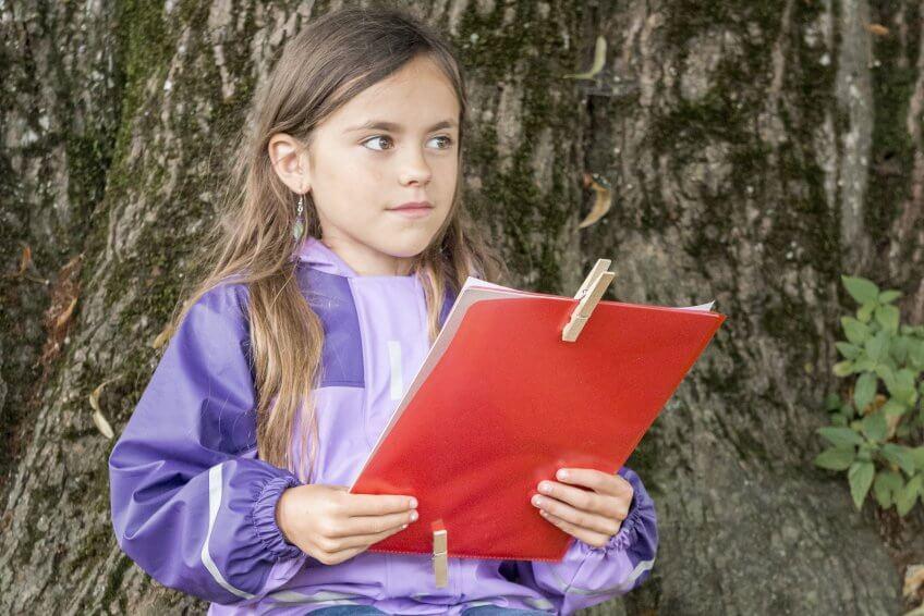 Une enfant raconte une histoire dans la nature.