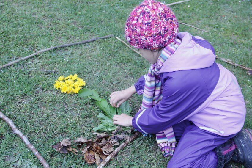 Une enfant façonne une image avec du matériel naturel.