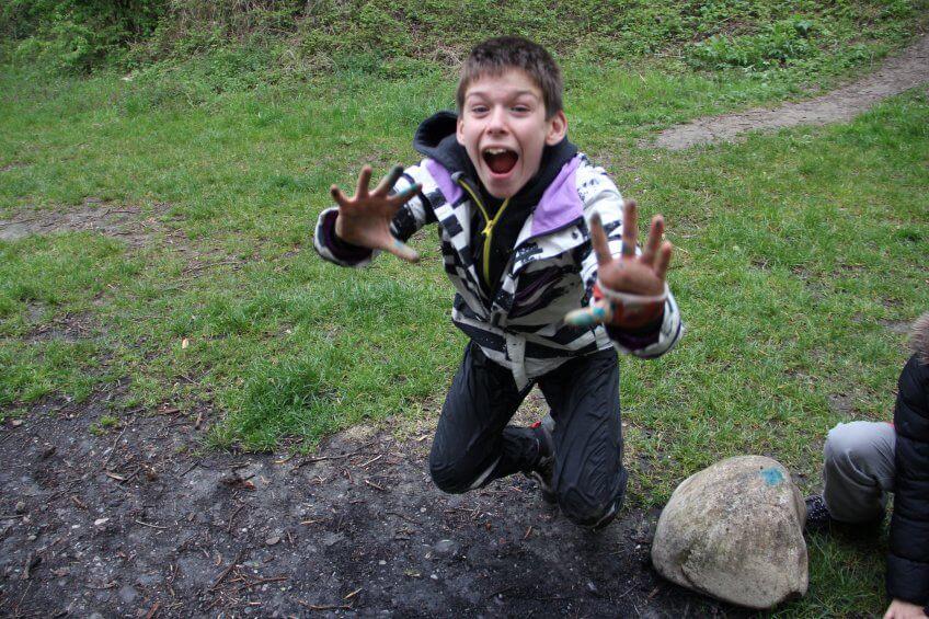 Un enfant mime une grenouille.