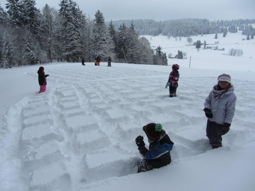 Les enfants font des carrés dans la neige.