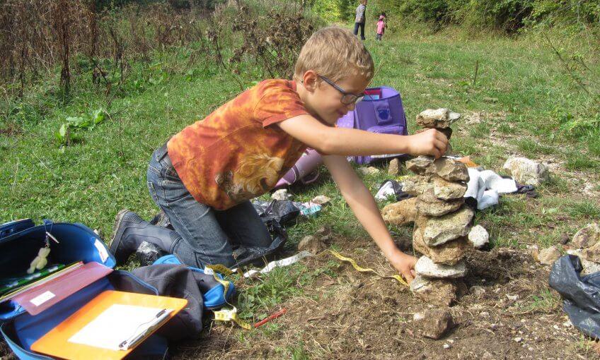 Un enfant qui mesure une tour en pierres.