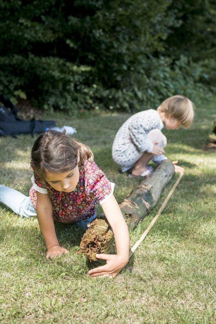 Deux enfants vérifient la longueur d'un tronc d'arbre.
