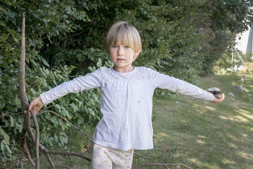 Une enfant comparant le poids d'une pierre et d'une branche d'arbre.