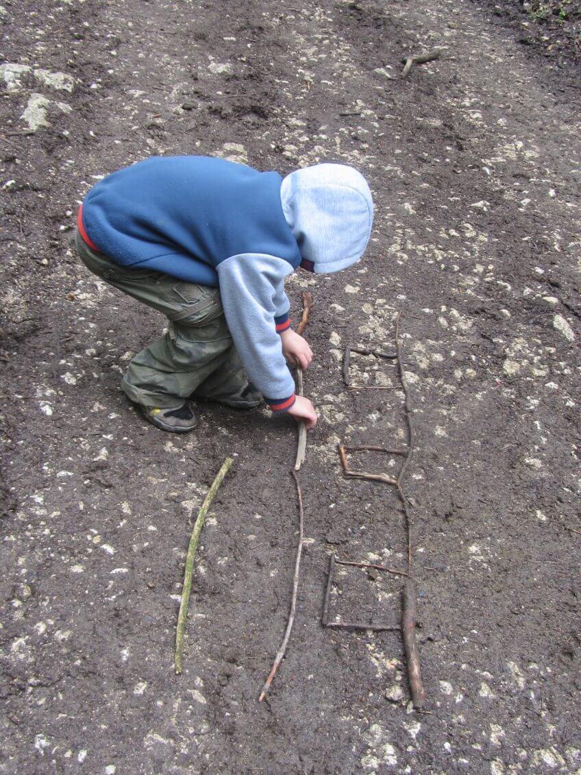 Un enfant avec un plan dessiné sur le sol.