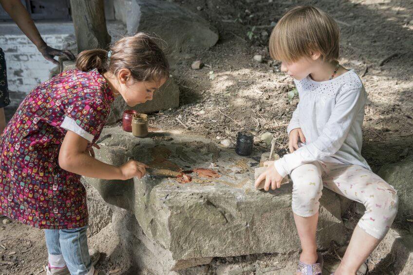 Des enfants dessinent avec de la terre.
