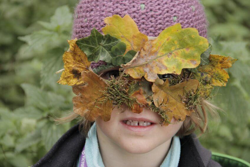 Une enfant avec masque en feuilles.