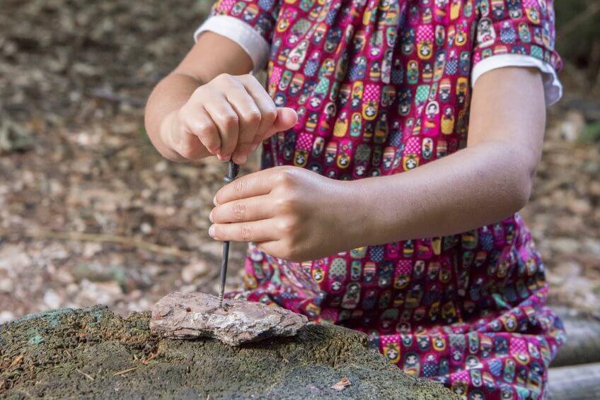 Une enfant qui fait un trou dans un cailloux.