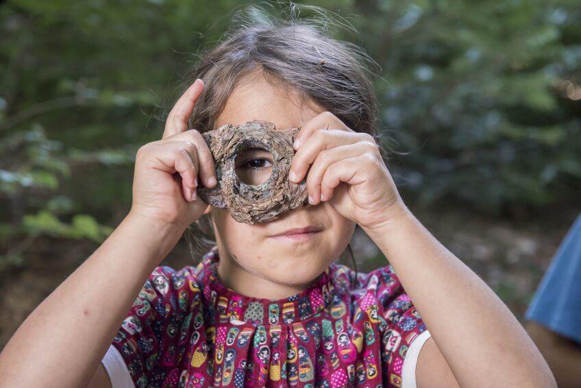Une enfant avec un appareil photo réalisé avec de l'écorce.