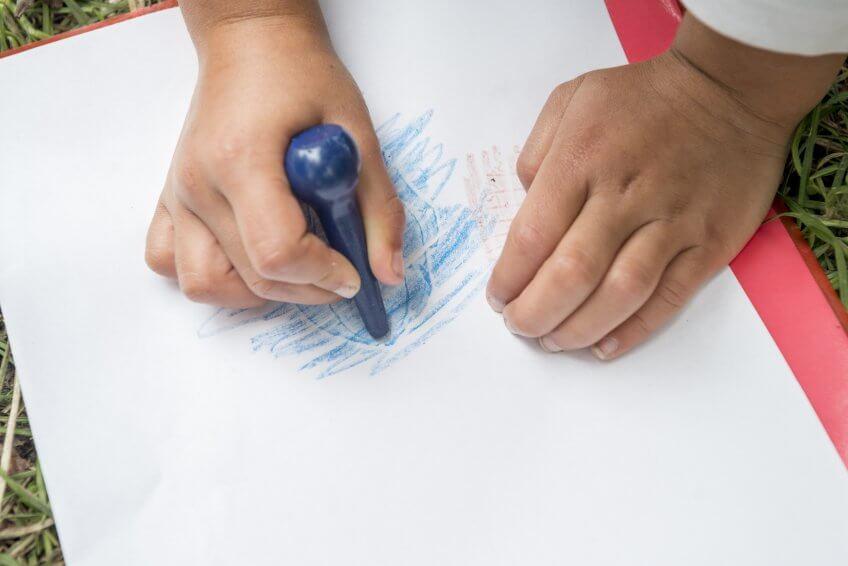 Un enfant décalque un dessin sur une feuille de papier.