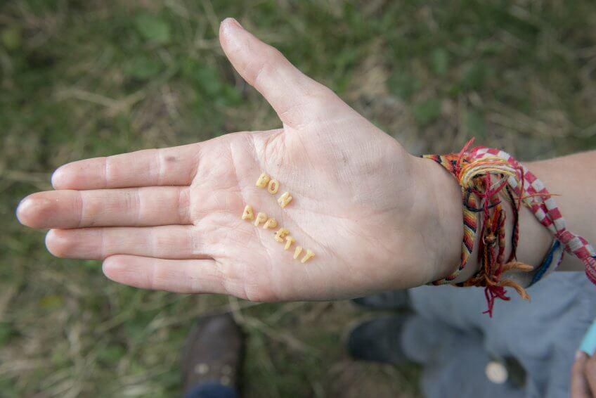 Des pâtes-lettres sur une main.