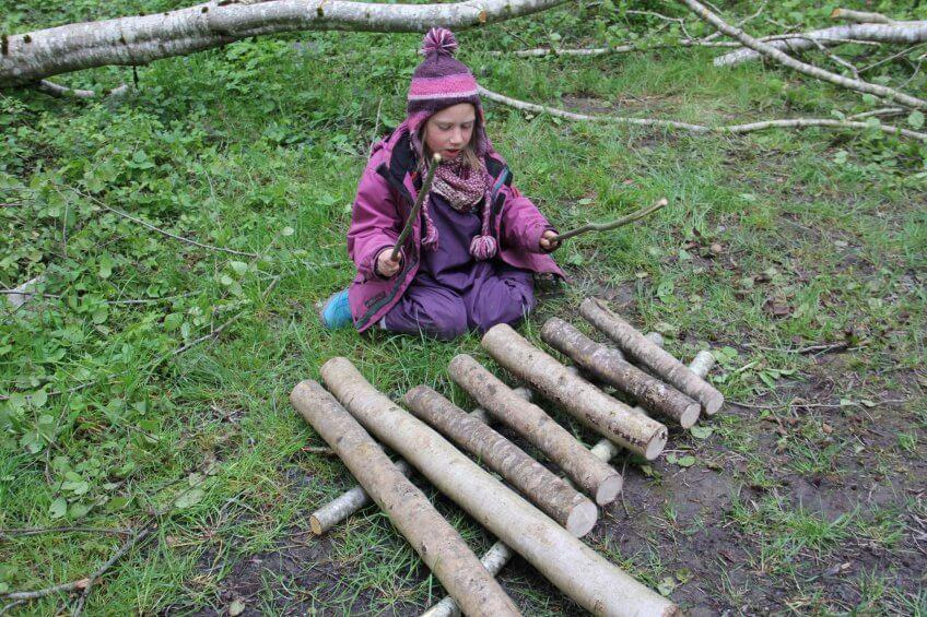 Une enfant avec un xylophone naturel.