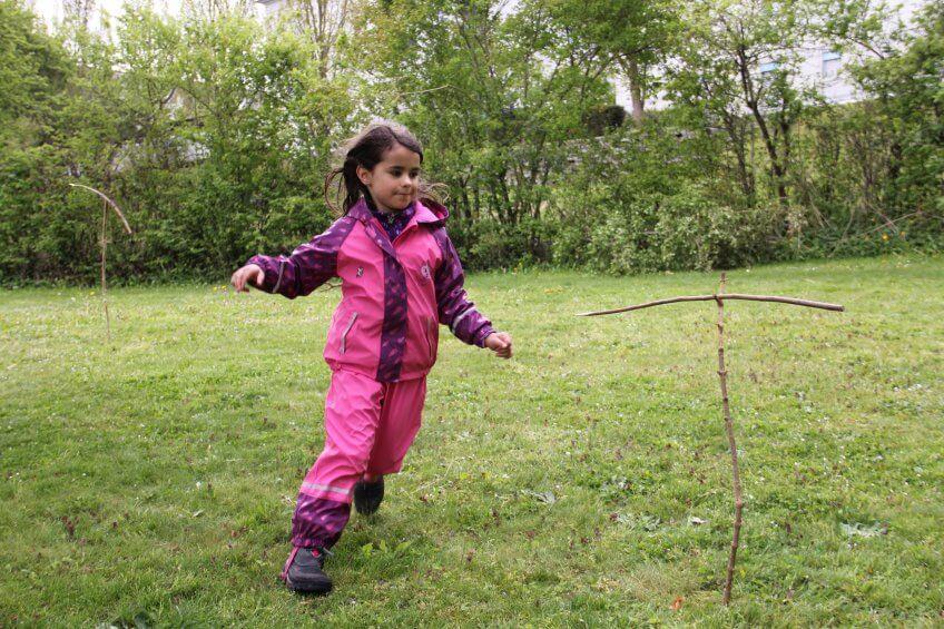 Une enfant slalome autour d'un bâton.